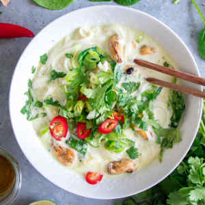 Thai green curry soup with mussels, noodles and coconut milk