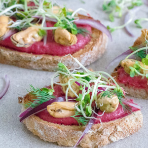 Smørrebrød with beet hummus, mussels in vinegar, red onion and dill