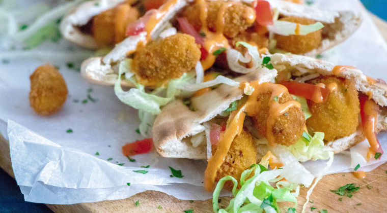 Pita bread with breaded mussels, iceberg lettuce, tomato and a spicy sauce